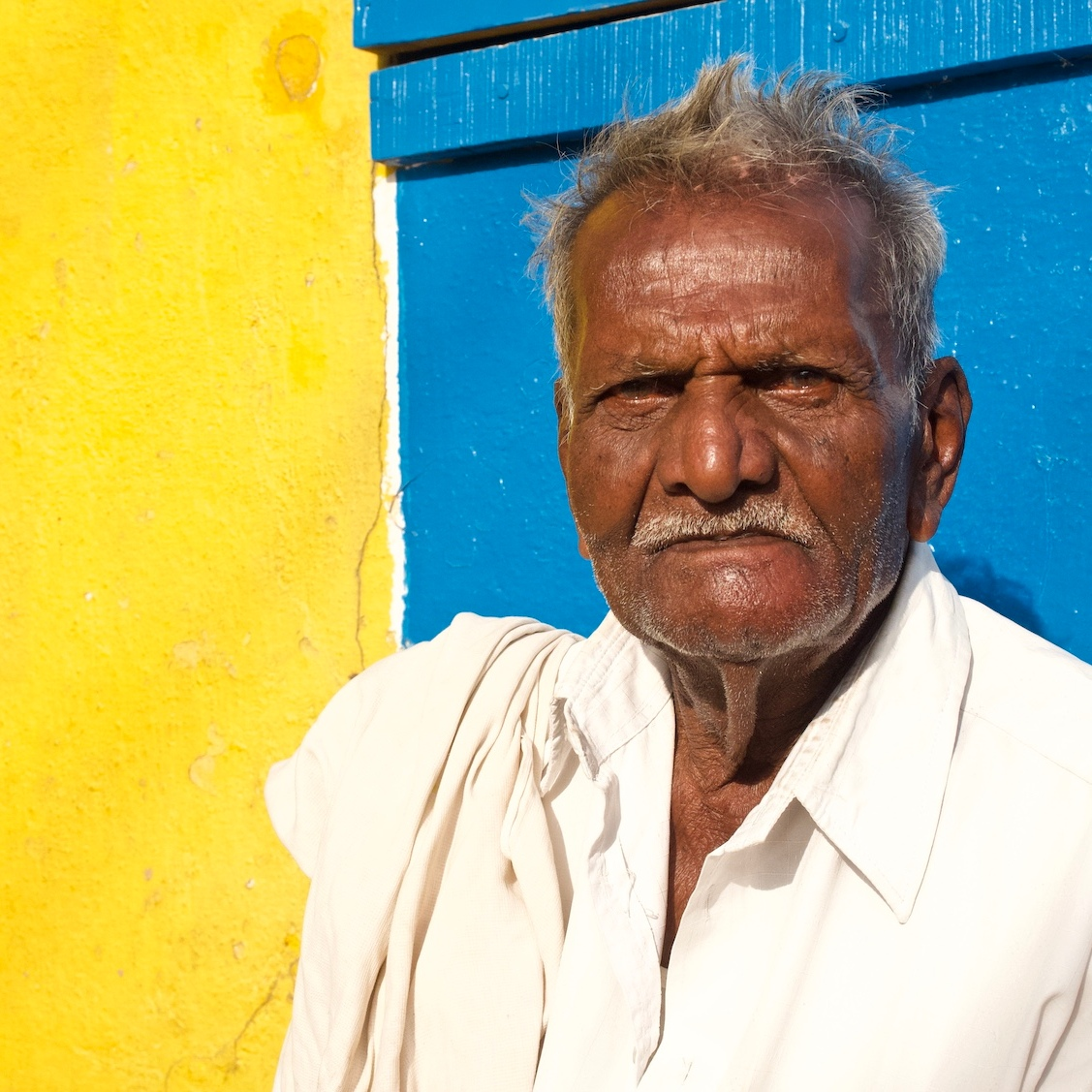 Old man with yellow and blue background.