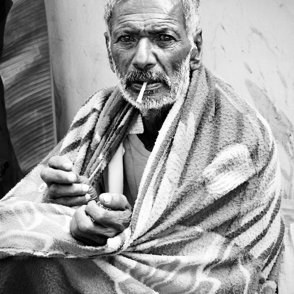 Man with glazed eyes and cigarette in his mouth.