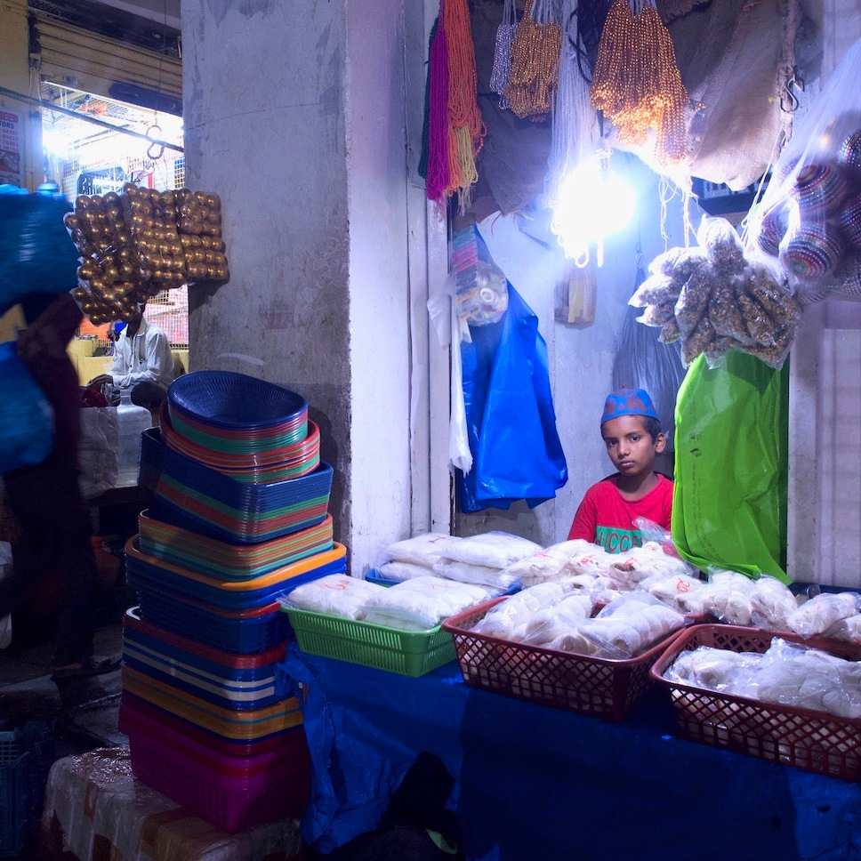 Young boy sitting under the light of a small shop.