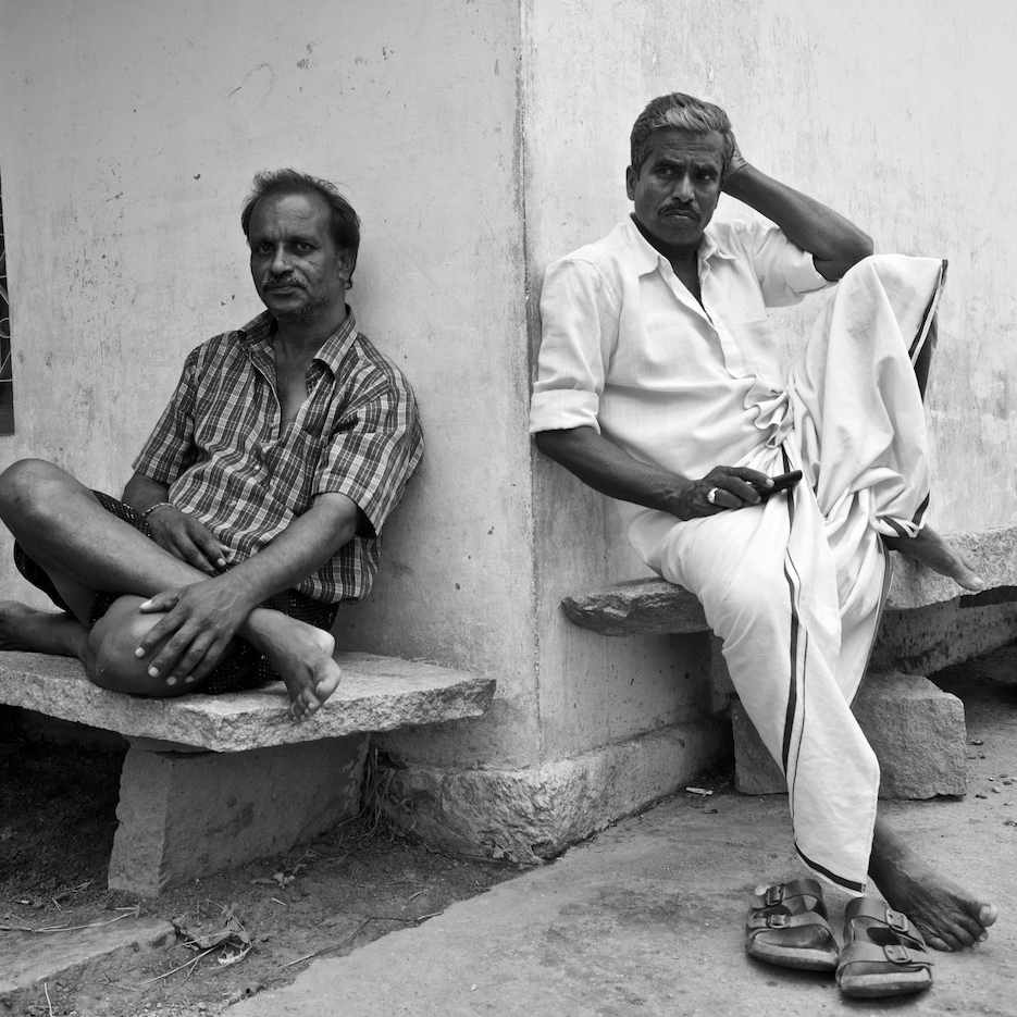 Two friends sitting at a crossroad.