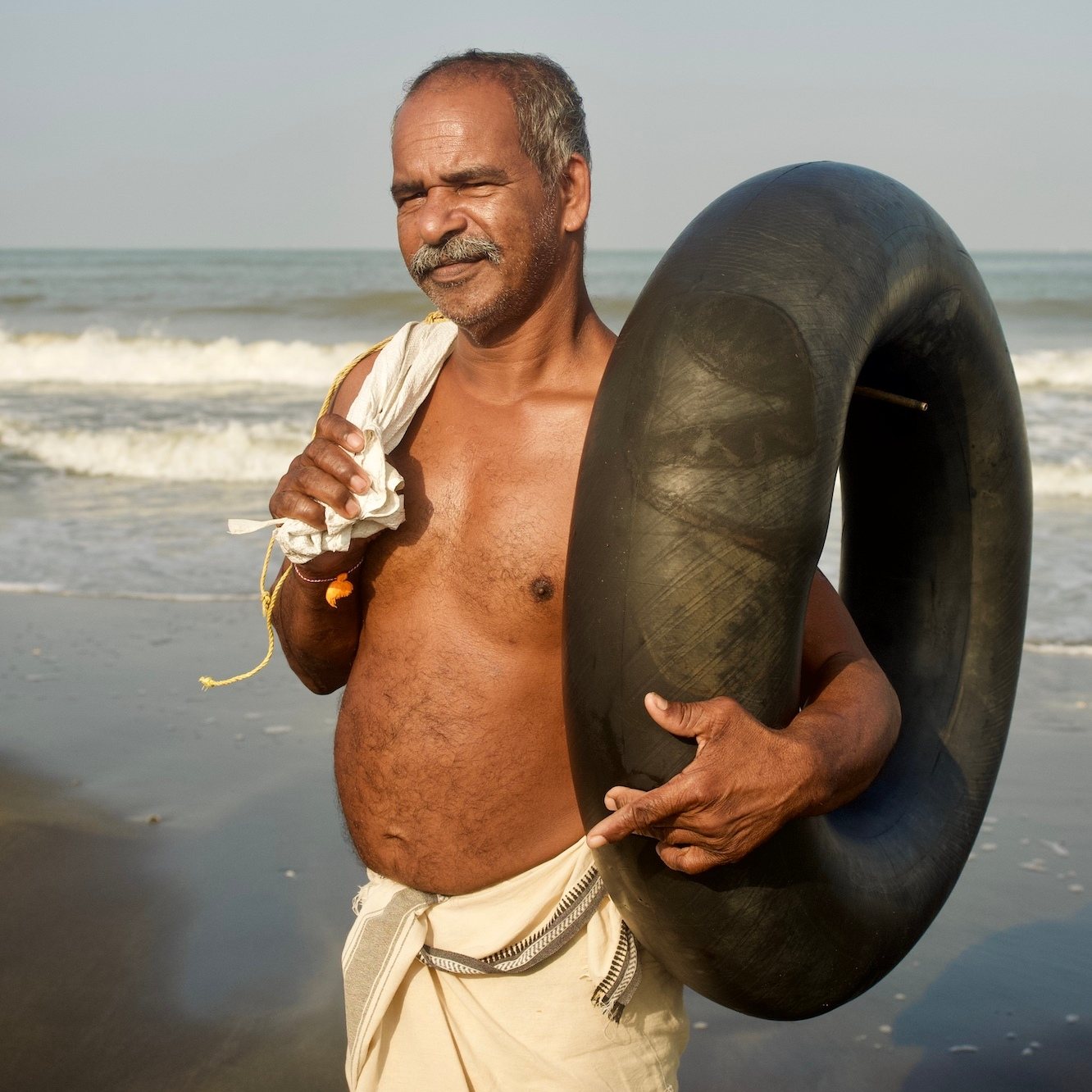Fisherman by the beach, holding a tyre.