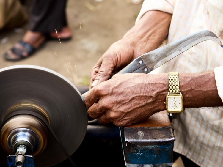 Knife Sharpener Wrinkled Hands sharpening a knife