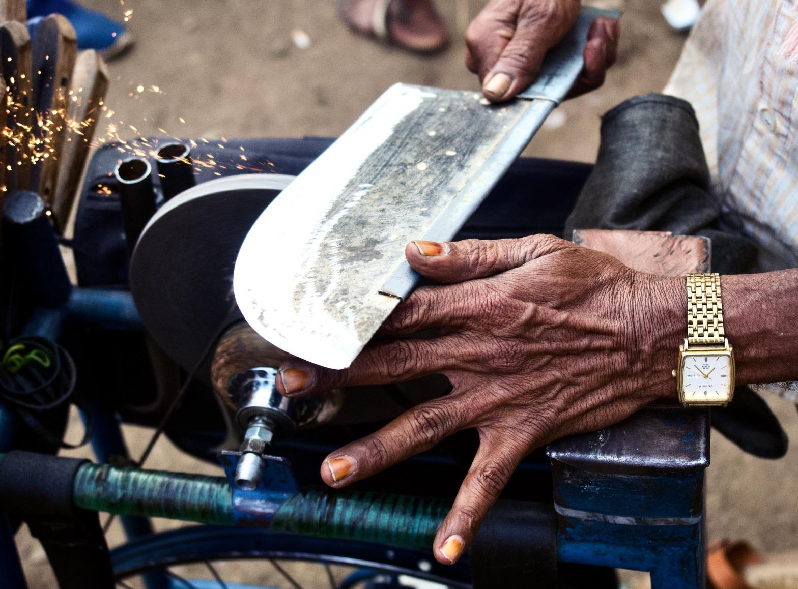 Wrinkled hands of a knife sharpener. Shot in Bangalore, Karnataka, India.